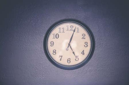 Foto de A watch hanging on the wall displaying five o'clock - Imagen libre de derechos