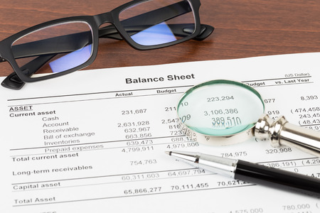 Photo pour Balance sheet financial report with glasses, and magnifier; document is mock-up - image libre de droit