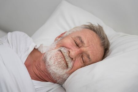 Photo for Senior elderly man sleeping happily with white blanket in bedroom - Royalty Free Image
