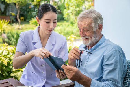 Photo for Senior elderly man reading book with nurse during breakfast in garden at nursing home - Royalty Free Image