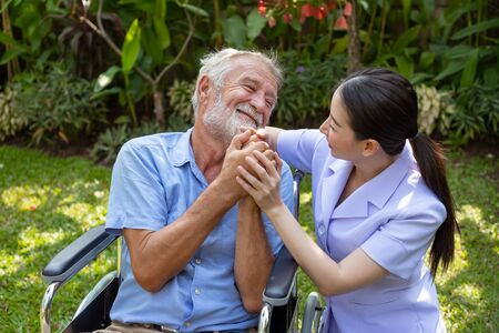 Photo pour Happy nurse holding elderly man hand on wheelchair in garden at nursing home - image libre de droit