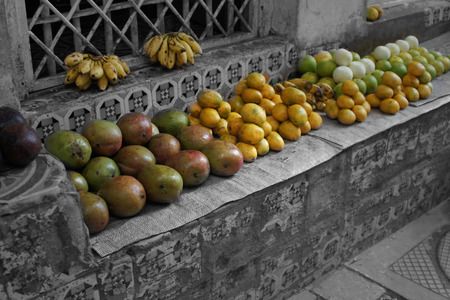 Tangerine and avocado are on a bench in front of a house. the fruit is colored, the background is black-wei.