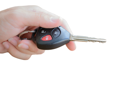 hand holding remote control of a car, key with alarm system, anti theft, isolate background