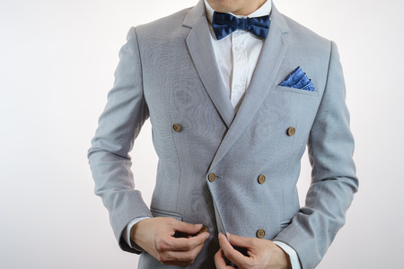 Man in grey suit, plaid texture, blue bowtie and pocket square, close up white background