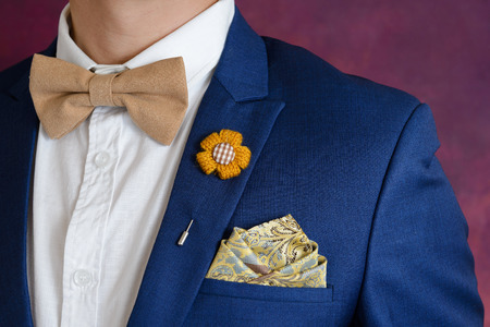 Man in blue suit with brown bow tie, flower brooch, and classic texture pocket square, close up