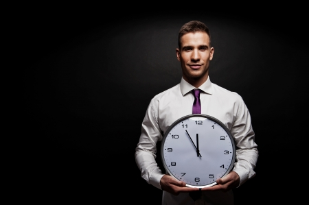 Man with wall clock over dark background