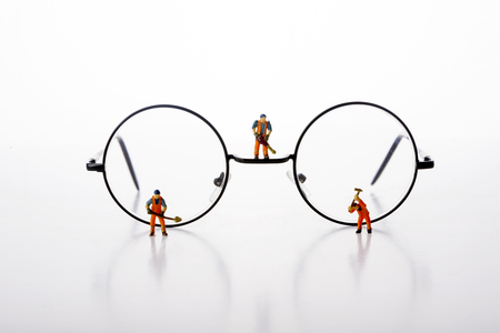 Miniature people workers walk by glasses over white background.