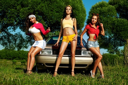 Three girl pin-up style near retro car at summer sunsetの写真素材