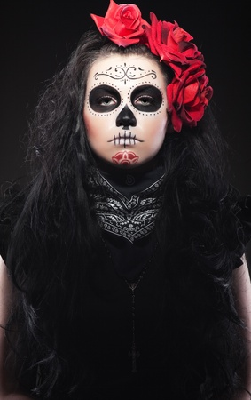 Serious woman in day of the skull mask