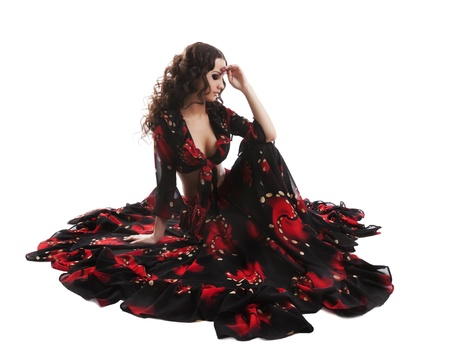 young cute woman sit in gypsy black and red costume isolated