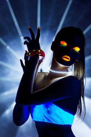 Girl with ultraviolet make-up disco dance in dark
