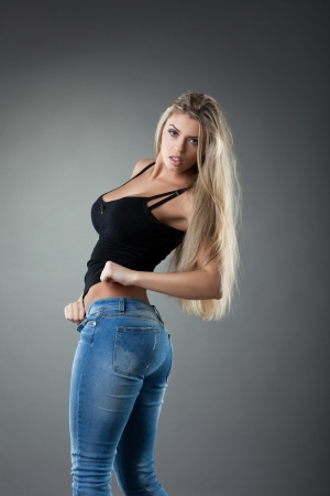 Studio portrait of sexy blonde young wonan in jeans