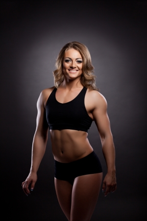 Young athletic woman body builder portrait in fitness costume