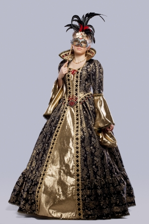 Full length portrait of young girl in carnival costume middle age with mask