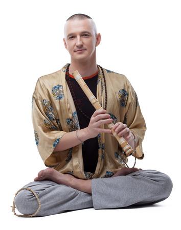 Yoga guru playing flute, isolated on white background