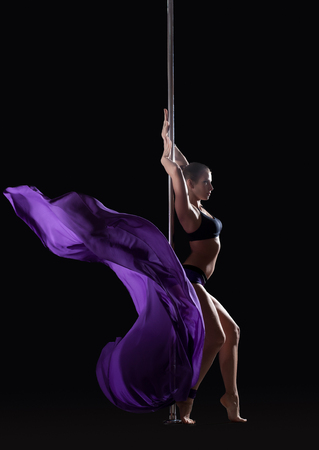 Young slim pole dancer posing with violet cloth, isolated on black