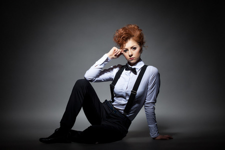Serious red-haired woman posing in office suit, on gray background