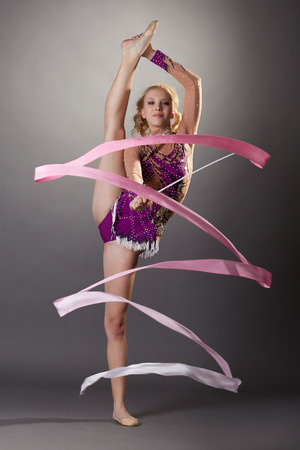 Studio shot of flexible young gymnast dancing with ribbon