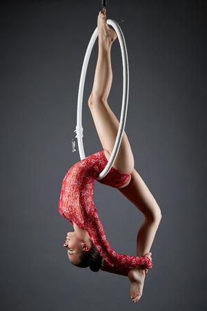 Studio photo of flexible dance performer on aerial hoop