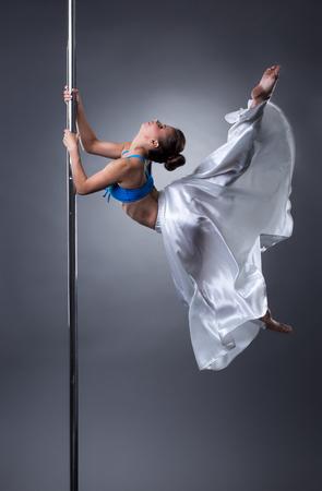 Sexy dancer turning gracefully around pole. Studio photo, on grey background