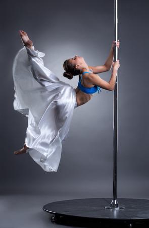 Image of beautiful girl turning gracefully around pylon
