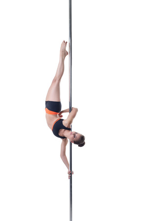 Image of pretty strong girl posing upside down on pylon
