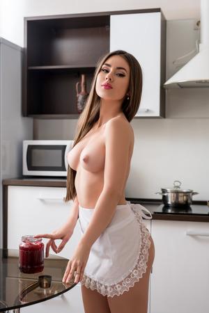 Foto de Image of beautiful topless model wearing maid's apron in kitchen - Imagen libre de derechos