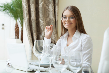 Cheerful business woman works on PC at her lunch, close-up