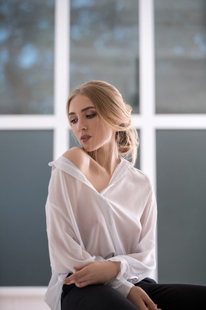 Woman in sexy white shirt posing on window sill