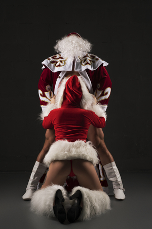 Sexy Snow Maiden on her knees before Santa Clause
