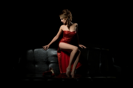 Photo pour Sexy girl in red dress relaxing on the sofa - image libre de droit