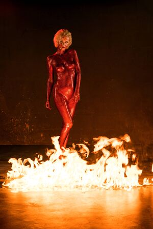 Photo pour Beautiful naked woman in red glitter near fire - image libre de droit