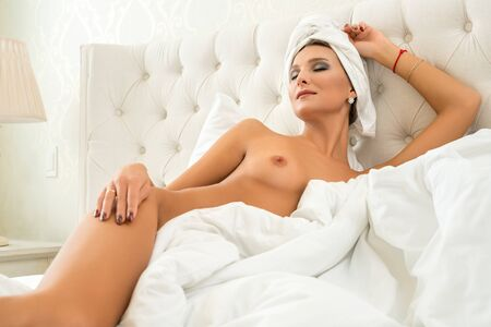 Foto de Gorgeous nude girl relaxing in bed view - Imagen libre de derechos