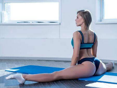 Photo pour In gym. Sexy girl posing while doing leg split - image libre de droit