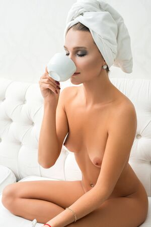 Photo pour Gorgeous nude girl having tea in bed view - image libre de droit
