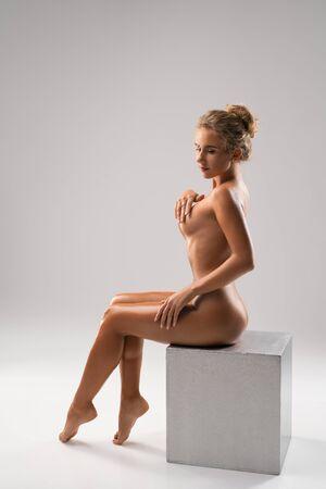 Foto de Nude beautiful woman sitting on the cube - Imagen libre de derechos