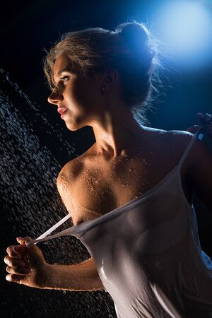 Blonde in wet t-shirt in shower view in the dark
