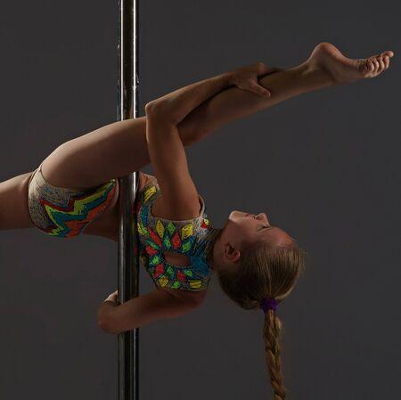 Photo pour Adorable little girl exercising on pylon in studio - image libre de droit