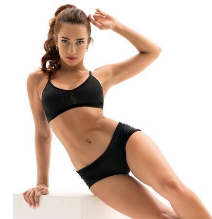 Photo pour Sportswoman posing with cube, isolated on white - image libre de droit