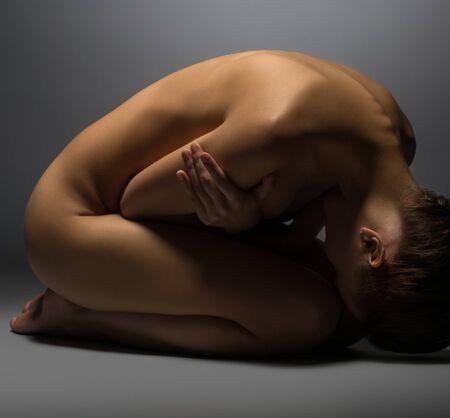 Foto de Naked woman lying on floor, hugging herself - Imagen libre de derechos