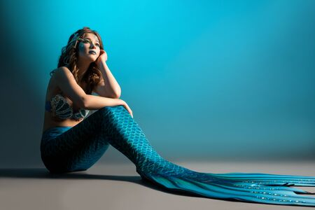 Photo for Woman in mermaid image sitting on the floor shot - Royalty Free Image
