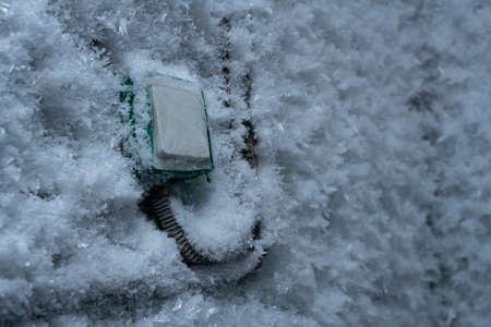 Foto de Snow covered device with switch on frozen wall in winter - Imagen libre de derechos