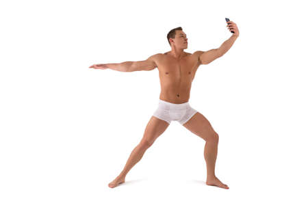 Photo pour Muscular shirtless man in yoga pose taking selfie on smartphone - image libre de droit