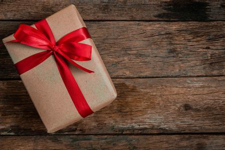 Foto de Brown Gift box bow tie Red ribbon On old wood floor top view merry christmas and happy new year concept - Imagen libre de derechos