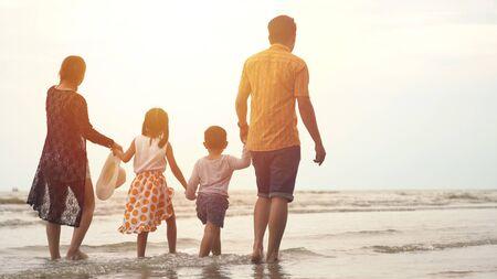 Photo pour Happy asian family enjoying walk on the beach - image libre de droit