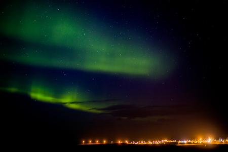 Photo pour Northern lights or aurora borealis over a city in Iceland - image libre de droit