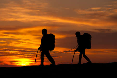 silhouette of two walking rock climbers on sunset sky
