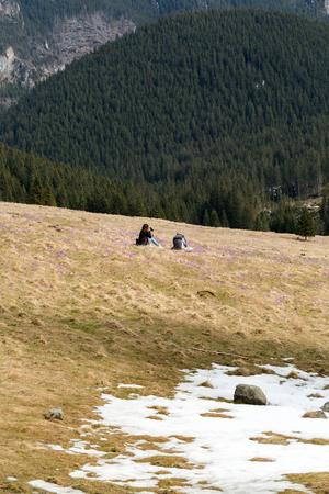 Happy hiking couple taking a break on mountain trail