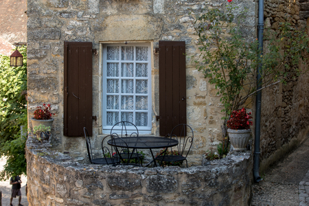 Photo pour A black metal table and chairs on the romantic terrace of an old stone house in Beynac-et-Cazenac, France - image libre de droit