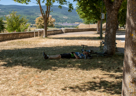 Sault, France - June 25, 2016: Cyclist resting in the shade of a tree in Sault. Provence, France